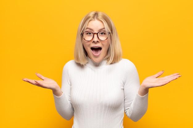 Блондинка выглядит счастливой и взволнованной, потрясенной неожиданным сюрпризом, с открытыми руками рядом с лицом