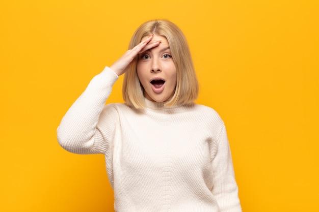Блондинка выглядит счастливой, удивленной и удивленной, улыбается и понимает удивительные и невероятно хорошие новости