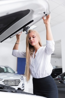 Blonde woman looking under hood of  car