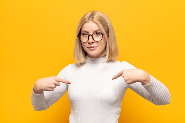 Blonde woman looking proud, positive and casual pointing to chest with both hands