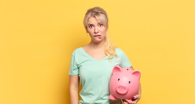 Blonde woman looking puzzled and confused, biting lip with a nervous gesture, not knowing the answer to the problem