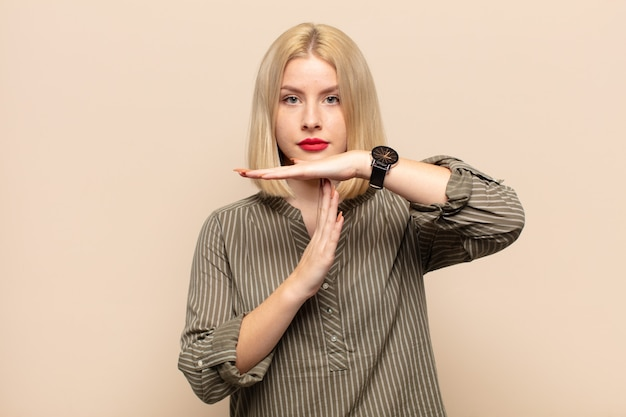 Blonde woman looking serious, stern, angry and displeased, making time out sign