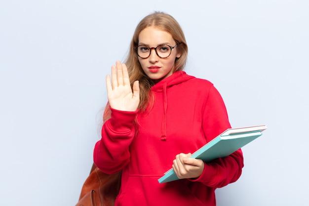 真面目で、厳しい、不機嫌で怒っている金髪の女性が開いた手のひらを停止ジェスチャーを示しています