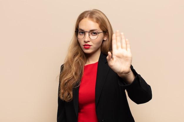 金髪の女性が真剣で、厳しく、不機嫌で、怒っているように見え、手のひらを広げて停止のジェスチャーをする
