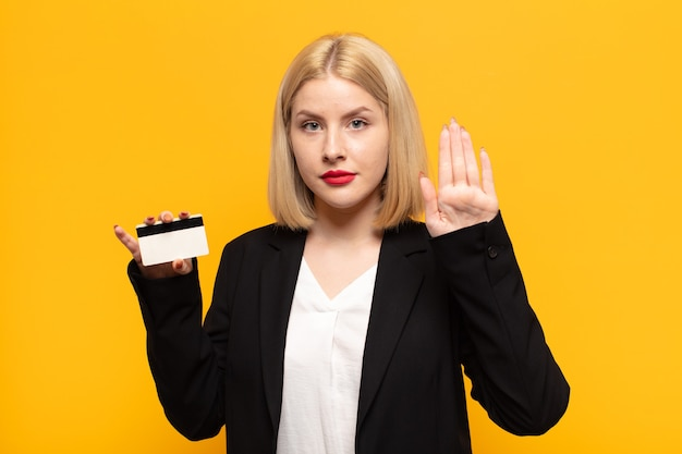Blonde woman looking serious, stern, displeased and angry showing open palm making stop gesture