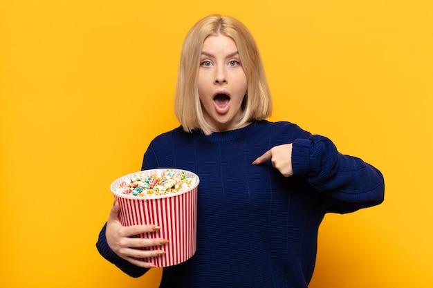 Блондинка выглядит шокированной и удивленной с широко открытым ртом, указывая на себя