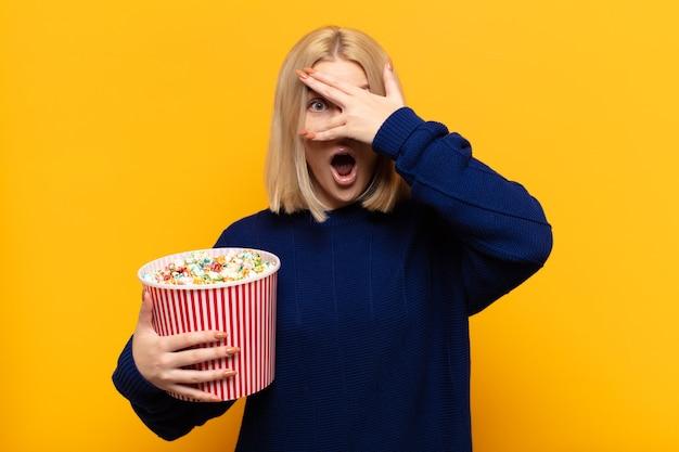 Блондинка выглядит шокированной, напуганной или напуганной, закрывает лицо рукой и заглядывает между пальцами