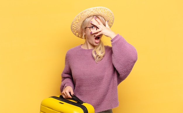 Blonde woman looking shocked, scared or terrified, covering face with hand and peeking between fingers