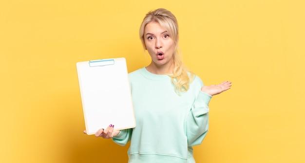 Блондинка выглядит удивленной и шокированной, с отвисшей челюстью, держащей предмет с открытой рукой сбоку