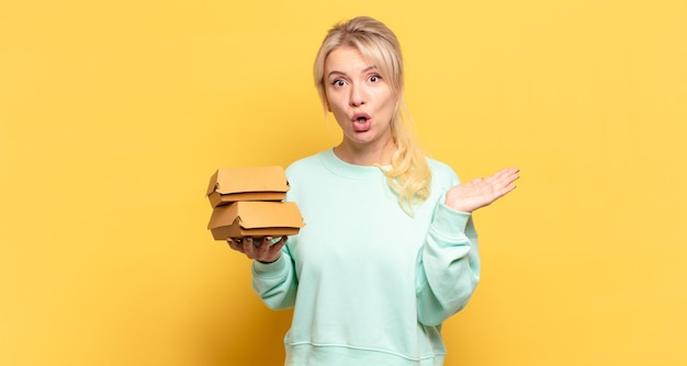Blonde woman looking surprised and shocked, with jaw dropped holding an object with an open hand on the side