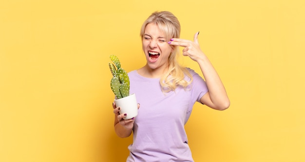 Blonde woman looking unhappy and stressed, suicide gesture making gun sign with hand, pointing to head