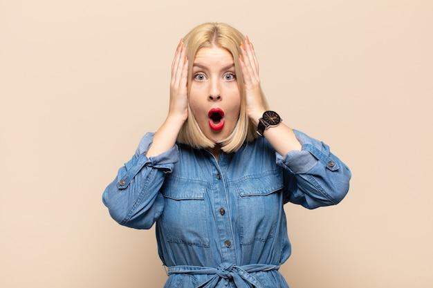 Блондинка выглядит неприятно шокированной, напуганной или обеспокоенной, с широко открытым ртом и закрывающей оба уха руками