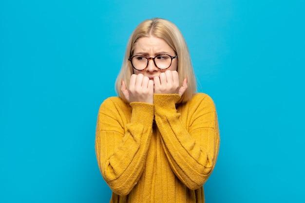 Блондинка выглядит обеспокоенной, встревоженной, напряженной и испуганной, кусает ногти и смотрит в пространство для боковой копии