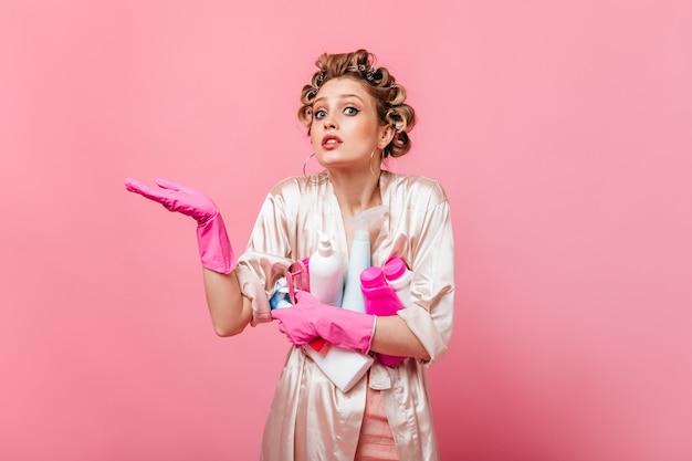 La donna bionda guarda davanti e tiene il detersivo sulla parete rosa
