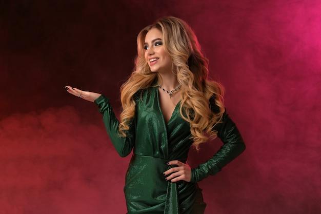 금발 여자, 메이크업, 녹색 세련된 드레스와 보석. 미소, 그녀의 손바닥에 뭔가 들고, 화려한 연기가 자욱한 배경에 포즈. 광고 및 디자인을 위한 템플릿 또는 모형. 확대