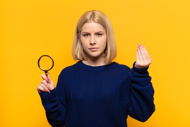 Blonde woman making capice or money gesture, telling you to pay your debts!