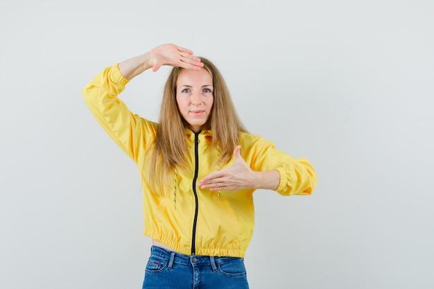 ジャケット、ジーンズ、陽気な探しでフレームジェスチャーを作るブロンドの女性、
