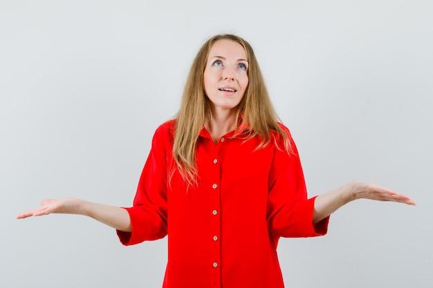 금발의여자가 빨간 셔츠에 비늘 제스처를 만들고 희망을 찾고.