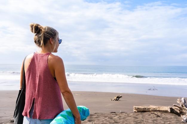 수평선을 바라보는 황량한 해변에 등을 대고 있는 금발의 여자