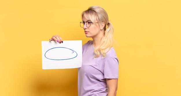 Блондинка в профиль смотрит, чтобы скопировать пространство впереди, думает, воображает или мечтает