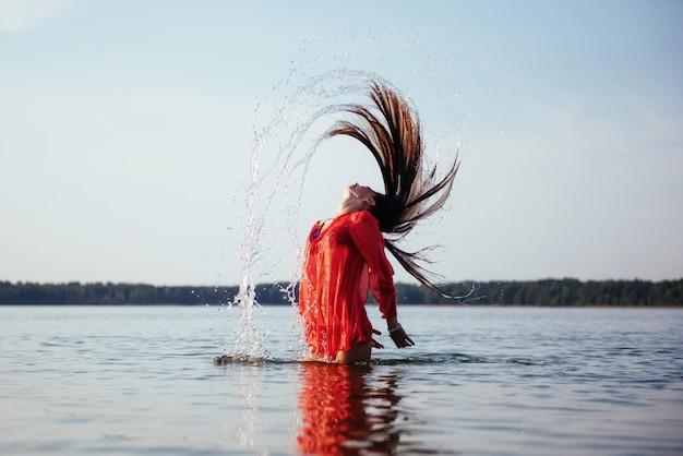 水の背景に金髪の女性