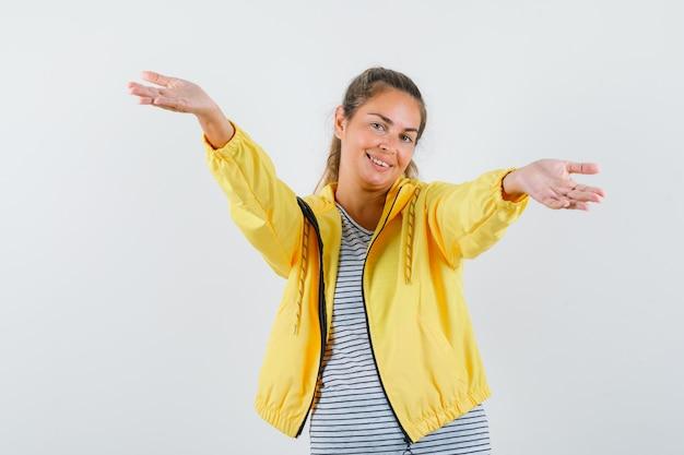 黄色のボンバージャケットとストライプのシャツで来て、きれいに見えるように誘うように腕を開くブロンドの女性