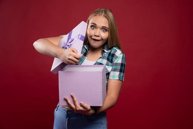 금발의 여자는 선물 상자를 열고 행복하고 웃습니다.
