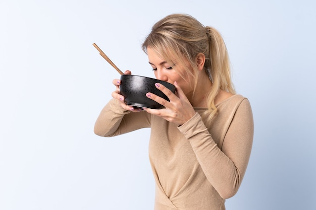 Блондинка женщина на изолированном синем фоне держит миску лапши с палочками для еды и ест ее