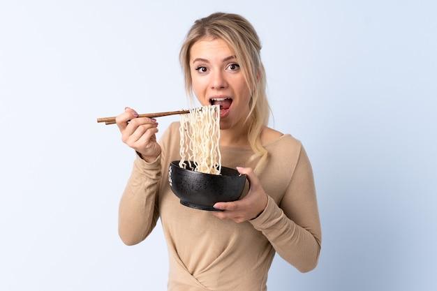 Блондинка над изолированным синим держит миску лапши палочками для еды и ест ее