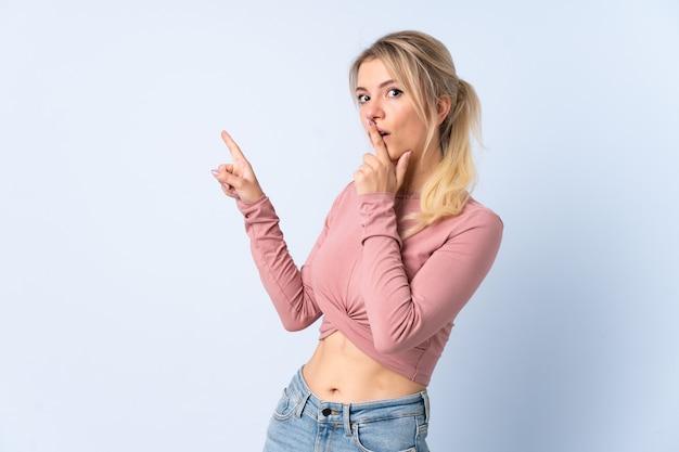 Блондинка над изолированной синей стеной с удивленным выражением лица, указывая сторону