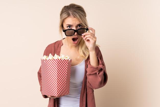 Блондинка над изолированной стеной удивлена 3d-очками и держит большое ведро попкорна