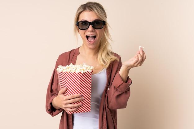 Блондинка над изолированной стеной в 3d-очках и держит большое ведро попкорна