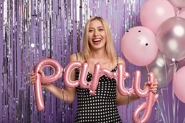 Donna bionda alla festa che tiene palloncini