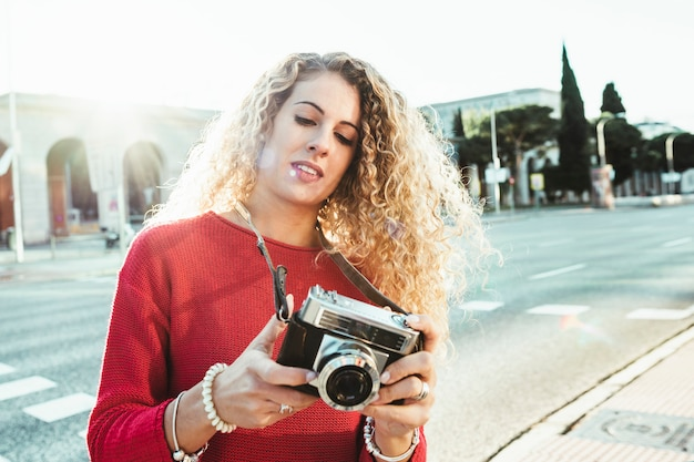 Blonde woman photographer who walks through the city at sunset traveling and sightseeing