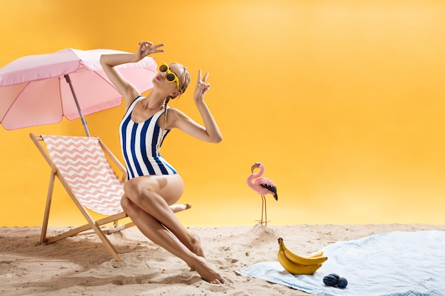 Blonde woman on pink chaise-longue poses with hands