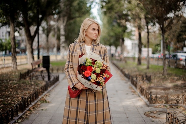 Blonde woman in plaid coat holding a bright bouquet of flowers standing on alley