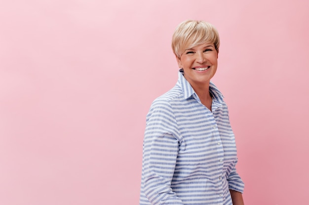 Blonde woman in plaid shirt laughing on pink background