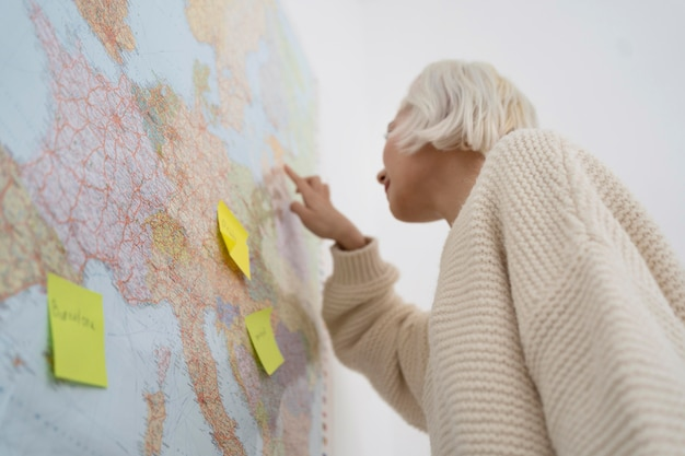 Blonde woman planning a trip with a map