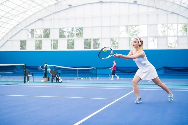 テニスをしているブロンドの女性