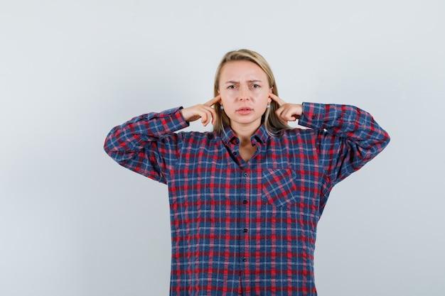 Donna bionda che collega le orecchie con il dito indice in camicia a quadri e sembra arrabbiato, vista frontale.