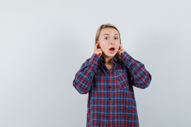 Donna bionda che tappando le orecchie con il dito indice in camicia a quadri e guardando sorpreso, vista frontale.