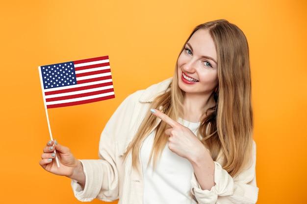 Блондинка показывает пальцем на маленький американский флаг и улыбается