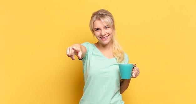 만족, 자신감, 친절한 미소로 앞에 가리키는 금발의 여자, 당신을 선택