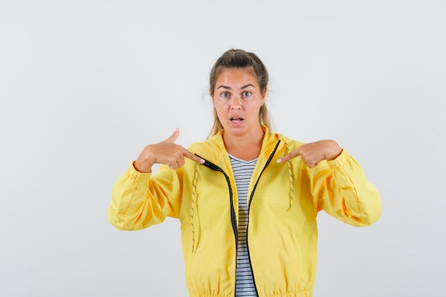 노란색 폭격기 재킷과 스트라이프 셔츠에 검지 손가락으로 자신을 가리키고 놀란 금발의 여자