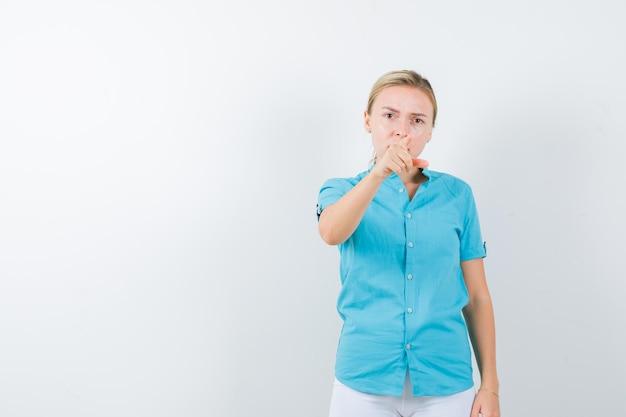 Donna bionda che punta alla telecamera in camicetta blu e sembra seria