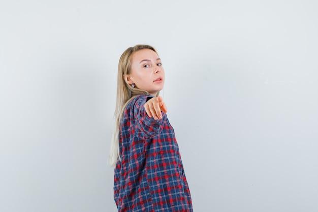 Donna bionda che punta alla telecamera con il dito indice in camicia a quadri e attraente, vista frontale.