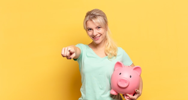Blonde woman pointing at camera with a satisfied, confident, friendly smile, choosing you