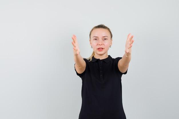 Donna bionda che punta davanti con entrambe le mani in maglietta nera e sembra ottimista