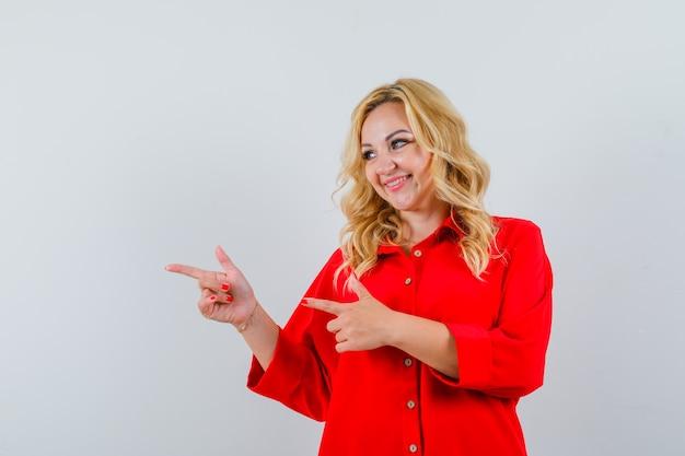 Donna bionda che punta a sinistra con il dito indice in camicetta rossa e che sembra felice.