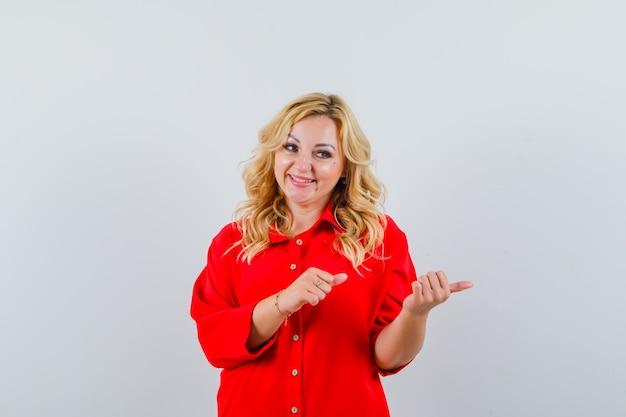 Donna bionda che indica il lato destro con il dito indice in camicetta rossa e che sembra felice.